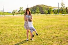 Glücklicher lachender kleiner Junge, der in der Natur mit Mutter spielt Lizenzfreie Stockbilder