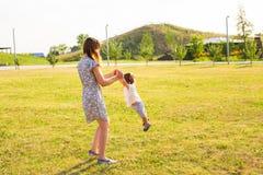 Glücklicher lachender kleiner Junge, der in der Natur mit Mutter spielt Lizenzfreies Stockbild