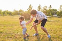 Glücklicher lachender kleiner Junge, der in der Natur mit Vater spielt Stockbilder