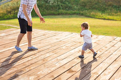 Glücklicher lachender kleiner Junge, der in der Natur mit Vater spielt Stockfotos