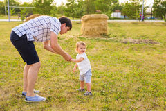 Glücklicher lachender kleiner Junge, der in der Natur mit Vater spielt Stockfotografie