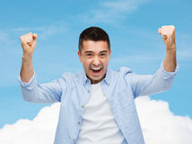Glücklicher lachender Mann mit den angehobenen Händen Stockfoto
