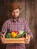 Glücklicher Landwirt, der Holzkiste Gemüse hält Stockbilder