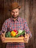 Glücklicher Landwirt, der Holzkiste Gemüse hält Stockfoto