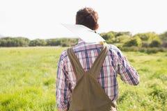 Glücklicher Landwirt, der seine Schaufel trägt Lizenzfreies Stockbild