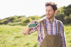 Glücklicher Landwirt, der seine Schaufel trägt Stockfoto