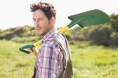 Glücklicher Landwirt, der seine Schaufel trägt Lizenzfreie Stockbilder