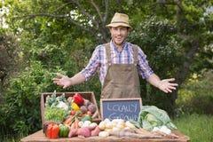 Glücklicher Landwirt, der seinem Erzeugnis zeigt lizenzfreie stockfotografie