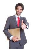 Glücklicher lateinischer Geschäftsmann mit der Datei, die Daumen zeigt Stockfotografie