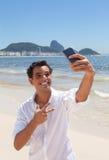 Glücklicher lateinischer Kerl, der selfie an Copacabana-Strand macht Stockbild