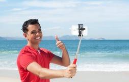 Glücklicher lateinischer Kerl am Strand ein Bild mit Telefon und selfie Stock sprechend Lizenzfreie Stockbilder