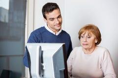 Glücklicher Lehrer Helping Senior Student in der Computer-Klasse Lizenzfreie Stockbilder