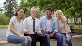 Glücklicher Lehrer und multiethnische Studenten, die auf der Bank, lächelnd in Kamera sitzen stockfotografie