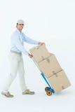 Glücklicher Lieferer, der Laufkatze von Pappschachteln drückt Stockbilder
