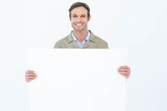Glücklicher Lieferer, der leere Anschlagtafel hält Stockfoto