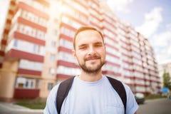 Glücklicher lustiger bärtiger Studentenmann im blauen T-Shirt mit dem Rucksack, der vor dem flachen Hausschlafsaal des Neubaus st Stockfotos
