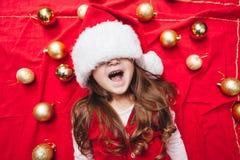 Glücklicher Mädchenabschluß ihre Augen mit Weihnachtshut lizenzfreie stockbilder