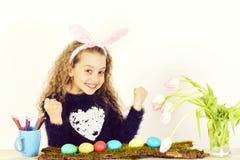 Glücklicher Mädchenmaler mit Bleistift, Tulpe blüht, bunte Ostereier lizenzfreie stockbilder