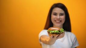 Glücklicher Mädchenvertretungshamburger zur Kamera, erfüllter Kunde des Schnellrestaurants stock video