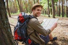 Glücklicher männlicher Abenteurer, der im Wald navigiert Lizenzfreie Stockbilder