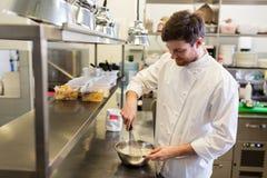 Glücklicher männlicher Chef, der Lebensmittel an der Restaurantküche kocht Stockbilder