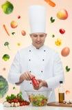 Glücklicher männlicher Chefkoch, der Lebensmittel kocht Stockfotografie