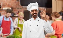 Glücklicher männlicher indischer Chef, der o.k. am Kochkurs darstellt stockfotos