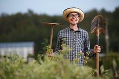 Glücklicher männlicher Landwirt mit Schaufel und Rührstange auf der Natur Lizenzfreies Stockfoto