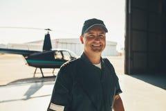 Glücklicher männlicher Pilot, der im Flugzeughangar steht Stockfotografie