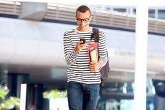 Glücklicher männlicher Student, der auf dem Campus mit Buchtasche und -Mobiltelefon geht lizenzfreie stockfotos