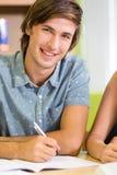 Glücklicher männlicher Student, der Hausarbeit in der Bibliothek tut Stockfotos