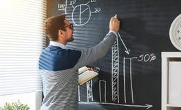 Glücklicher männlicher Student, Lehrer, Freiberufler mit Kreide an der Tafel lizenzfreies stockbild