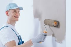 Glücklicher Maler, der die Wand malt stockbilder