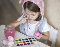 Glücklicher Maler kleinen Mädchens Ostern in den rosa Häschenohren mit bunten gemalten Eiern Ein Kind, das für Ostern sich vorber lizenzfreies stockfoto