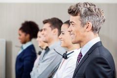 Glücklicher Manager Standing In Row mit Call-Center Stockfotos