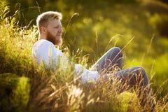 Glücklicher Mann auf dem Gras und Blicke in den Abstand Stockfotografie