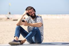Glücklicher Mann in den Kopfhörern, die auf Strand mit Lächeln sitzen Lizenzfreies Stockfoto