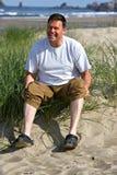 Glücklicher Mann an den weißen Fahrwerkbeinen des Strandes Stockfotos