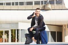Glücklicher Mann, der außerhalb der Station mit Gepäck am Telefon wartet Stockfotos
