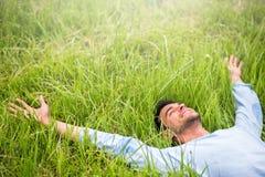 Glücklicher Mann, der auf dem grünen Gras mit den Armen ausgestreckt liegt lizenzfreies stockbild
