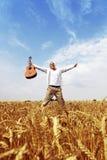 Glücklicher Mann, der auf einem Weizengebiet springt stockfotos