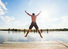 Glücklicher Mann, der auf Pier springt stockbild