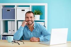 Glücklicher Mann, der auf seiner Hand arbeitet im Büro sich lehnt lizenzfreies stockfoto