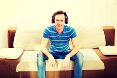 Glücklicher Mann, der auf Sofa und hörender Musik sitzt stockfotografie