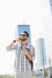 Glücklicher Mann, der bei der Anwendung des Handys in der Stadt weg schaut Stockbild