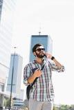 Glücklicher Mann, der bei der Anwendung des Handys in der Stadt weg schaut Lizenzfreie Stockfotos
