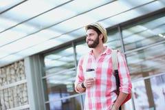 Glücklicher Mann, der beim Halten der Wegwerfschale in der Stadt weg schaut Stockbilder