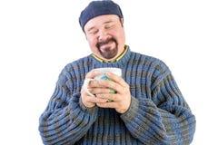 Glücklicher Mann in der blauen Strickjacke mit Heißgetränk Stockbild