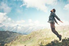 Glücklicher Mann, der an den Bergen zum Wolkenhimmel springt stockfotos