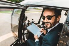 Glücklicher Mann, der die Dokumente im Hubschrauber lächelt und unterzeichnet stockfoto